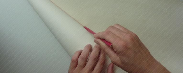 An der eingerollten Papiertüte wird eine Linie entlang gezogen